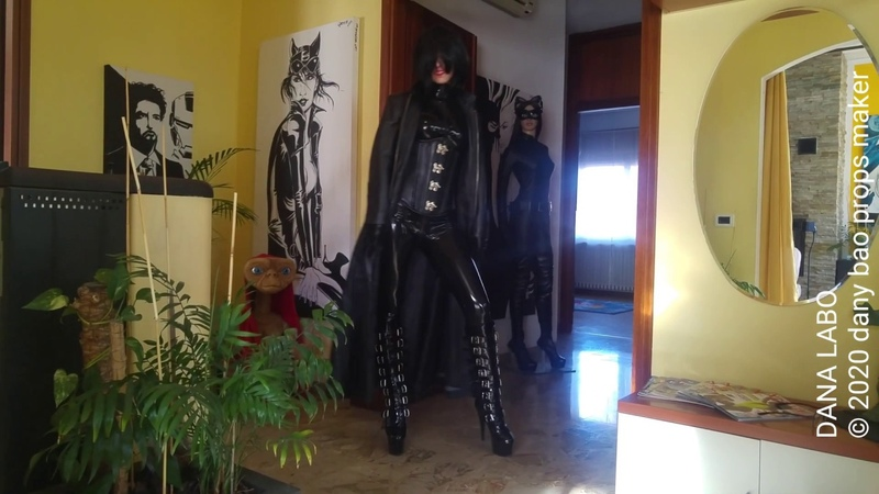 DANA LABO - the woman in black, latex catsuit, gloves, corset, coat and shinny boots,