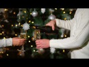 Man and woman are pouring champagne in glasses standing near Christmas tree