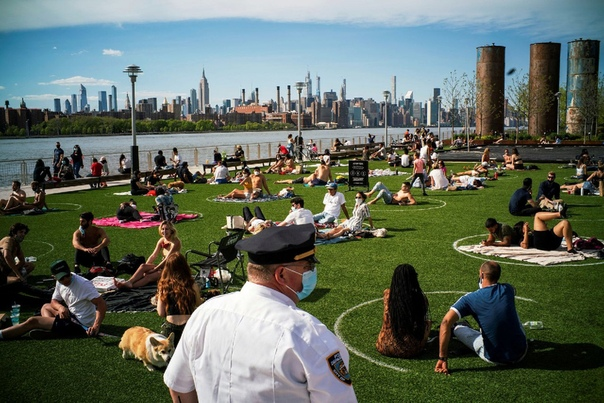 Полицейский патрулирует парк Домино в Бруклине, чтобы проверить, соблюдают ли люди правила физического дистанцирования