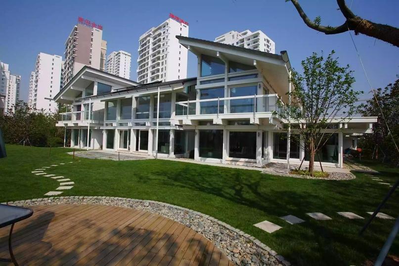 Дом Huf Haus в Китае, жилые многоэтажки на заднем плане, деревянный дворик на переднем плане