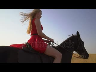 Stock-footage-young-blonde-girl-horseback-rider-in-red-dress-riding-horse-on-country-road-side-view-of